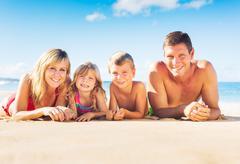 family of four on tropical beach - stock photo