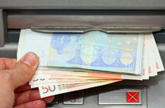 money euro cash withdrawal from an atm of the airport - stock photo