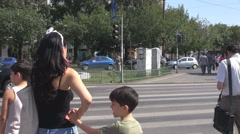People wait green light color at pedestrian semaphore, cars move on same street Stock Footage