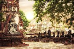 Buddha at wat mahathat ruins under sunset sky. ayutthaya, thailand travel Stock Photos