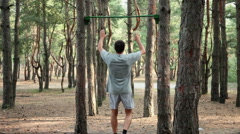 Workout pull-ups in pine forest Stock Footage
