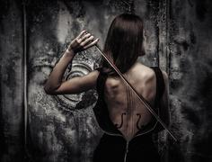 Woman in dress with violin body art holding bow Stock Photos