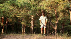 Man play with a dog in pine fores at evening Stock Footage