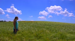 A young girl walks along a dirt road near a field of wildflowers. Stock Footage