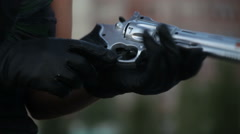 Woman in black gloves wearing a mini dress with a gun in her hands outdoors Stock Footage