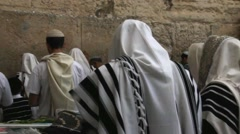 Many religious Jews in traditional white praying robe near Western Wall Stock Footage
