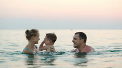 Happy family of three bathing in sea Stock Footage