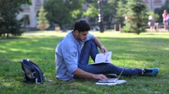 Handsome male student is reading book and working on laptop on campus Stock Footage