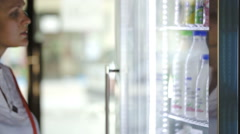 Woman choosing milk at the shop - stock footage