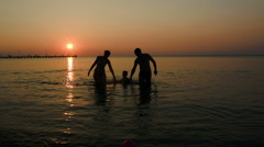 Family silhouettes coming out of sea at sunset three people Stock Footage