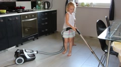 Little girl cleans a kitchen with vacum cleaner - stock footage