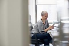 A woman working in an office alone, checking her smart phone. Stock Photos