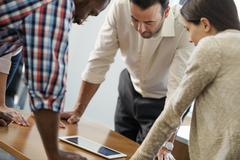 Four people leaning on a table at a meeting Stock Photos