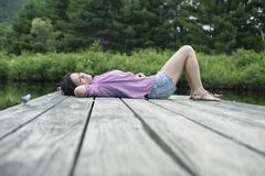 A woman lying on the jetty by a lake in summer Stock Photos
