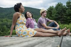 A group of people sitting on a woode pier overlooking a lake. Stock Photos