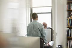 Stock Photo of office life. two people, businessmen talking to each other over their desks.