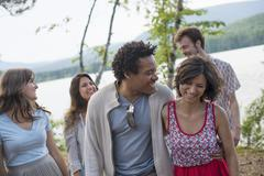 a group of people enjoying a leisurely walk by a lake. - stock photo