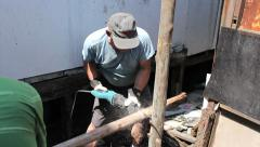 Man Using Saw To Cut Post In The Slums Stock Footage