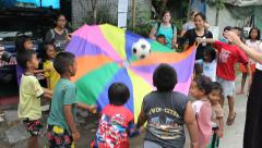 Youth Missions Team Playing Parachute Games With Slum Kids - stock footage