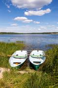 Lake scenery with two wooden boat in summertime Stock Photos