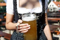 Young woman holding a beer mug in the beer garden Stock Photos