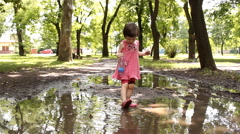 Cute little girl playing in the puddle of mud Stock Footage