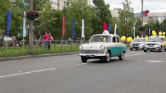 Old taxi car is on the head of procession. Parade is on the Kolpino town streets Stock Footage