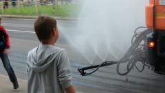 Watering trucks with water sprays pass city streets with children play around Stock Footage