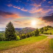 Follow the rainbow in high land at sunset Stock Photos