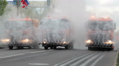 Watering trucks with water sprays up pass city streets. Kolpino city day, Russia Stock Footage