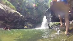 Man jumping into the river next to beautiful waterfall Stock Footage