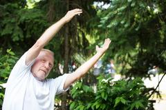 Closeup portrait, senior mature man in white shirt, stretching arms, isolated Stock Photos