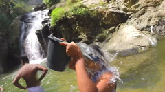 Slow motion of woman standing in the river pouring water from the bucket Stock Footage