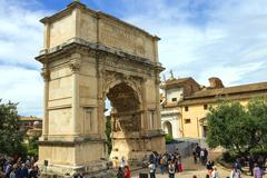 Tourists in square near the triumphal arch of titus in rome, italy Stock Photos