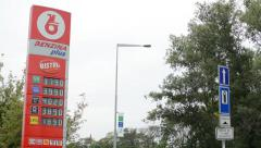 Fuel station - passing cars - trees and grass -information panel with fuel price Stock Footage