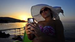 Beautiful model taking selfie pictures with smartphone at sunset. model lit w Stock Footage