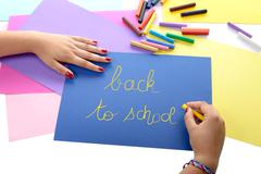 A girl writing back to school on blue paper Stock Photos
