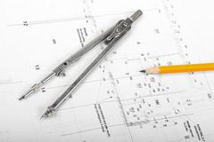 divider and pencil on architectural blueprints - stock photo