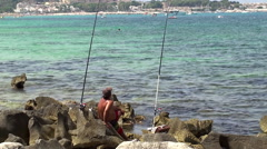 Angler is fishing on a wild rocky beach in the Mediterranean sea Stock Footage