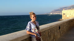 Girl smiling and waving to the camera, Trapani quay. Sicily, Italy. Stock Footage
