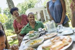A family gathering, men, women and children around a table in a garden in sum Stock Photos
