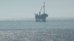 Off Shore Oil Platform in the Distance on the ocean silhouetted Stock Footage