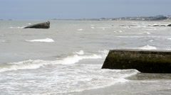 Arromanches les Bains beach with the remains of the Mulberry harbour in Normandy Stock Footage