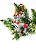 christmas tree holiday ornament hanging from a evergreen branch - stock photo
