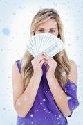 Stock Illustration of Composite image of blonde woman hiding her face behind a fan of notes