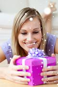 Stock Photo of Composite image of jolly woman holding a gift