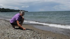 Female beachcomber looking at shells on the shore Stock Footage