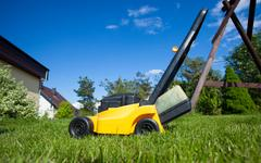Gardening. mowing lawn with yellow lawnmower Stock Photos