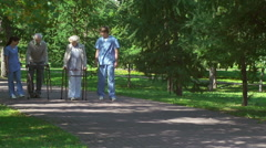 Patients with Walkers Accompanied by Caregivers Stock Footage