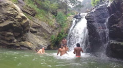 Slow motion of relaxed people standing in the river in front of waterfall. Stock Footage